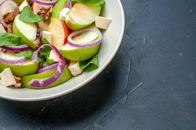 Vue de la moitié inférieure de la salade de pommes avec de l'oignon et d'autres aliments sur une assiette creuse sur une table sombre