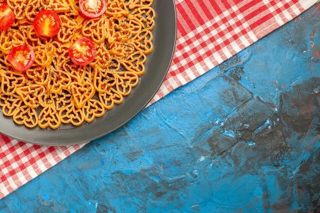 Vue de la moitié supérieure des coeurs de pâtes italiennes coupées de tomates cerises sur une plaque ovale sur une nappe à carreaux rouges et blancs