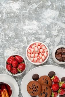 Vue de la moitié supérieure cookies fraises et chocolats ronds sur la plaque ovale arrondie avec des bols de bonbons fraises chocolats thé à la cannelle au bas de la table gris-blanc