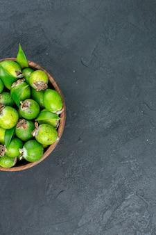 Vue de la moitié supérieure des feijoas frais dans un seau sur une surface sombre avec copie espace
