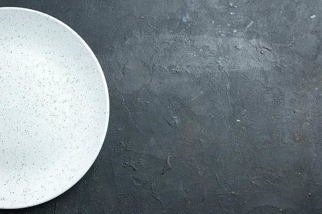 Vue de la moitié supérieure de la plaque ronde blanche sur une surface sombre avec place libre