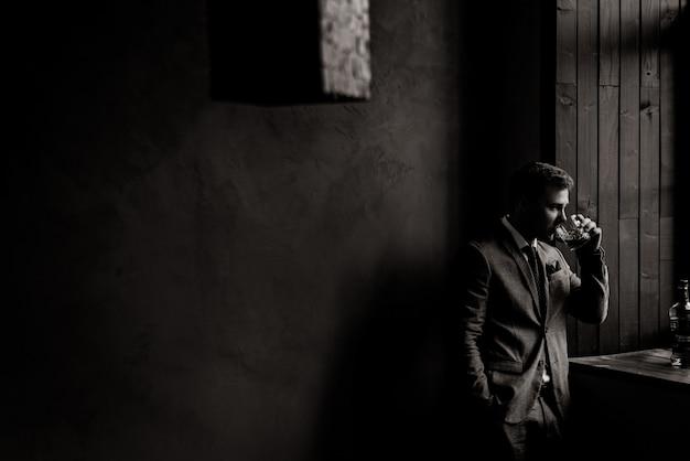 Vue monochrome de bel homme d'affaires dans la salle boit de l'alcool près de la fenêtre
