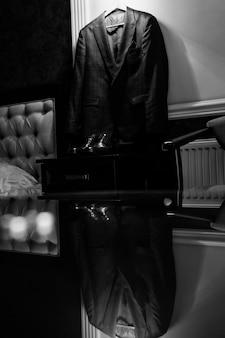 Vue monochrome de la tenue de mariage pour un marié se reflétant sur la table en verre