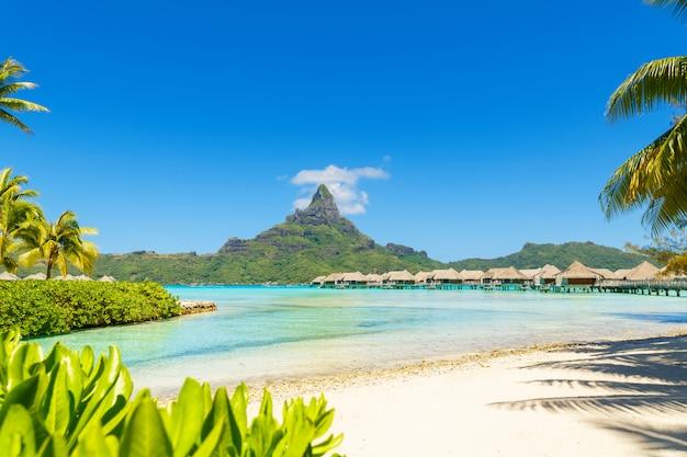 Vue sur le mont otemanu à travers un lagon turquoise et des bungalows sur pilotis sur l'île tropicale de bora bora, tahiti, polynésie française, océan pacifique,