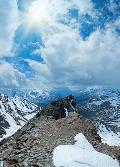 Vue sur la montagne depuis la station supérieure du téléphérique de karlesjoch (3108 m., près de kaunertal gletscher à la frontière austro-italienne) avec des fleurs d'alpage sur un précipice et des nuages