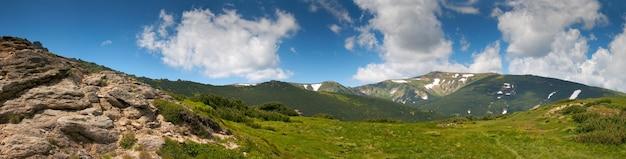 Vue sur la montagne d'été avec neige et grosses pierres à flanc de montagne. quatre clichés piquent l'image.