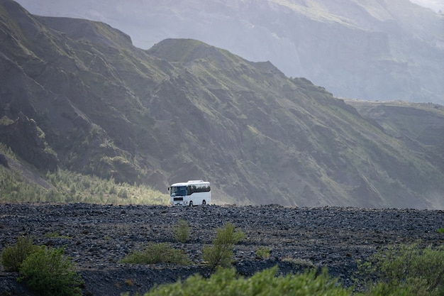 Vue sur la montagne d'islande avec gros bus. en attente de touristes.