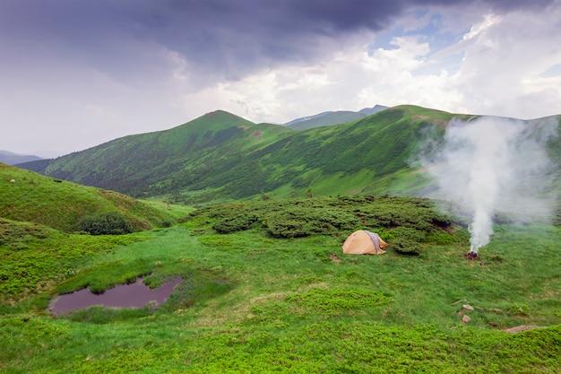 Vue sur la montagne avec une tente, un feu de camping et un petit lac en face