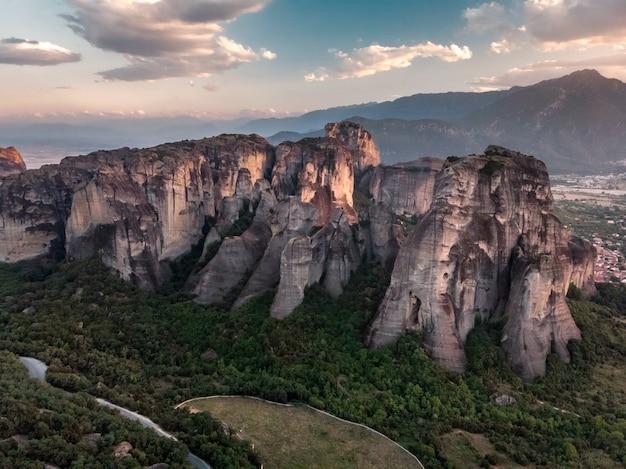 Vue sur les montagnes et la forêt verte contre le ciel bleu épique avec des nuages