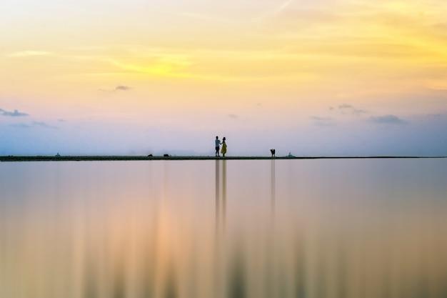 Vue naturelle panoramique du ciel au crépuscule et du jeune couple pendant le coucher du soleil.