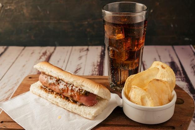 Vue neutre d'un hot-dog avec sauce chimichurri avec soda et chips sur une table rustique. plan horizontal. concept de restauration rapide et de malbouffe.