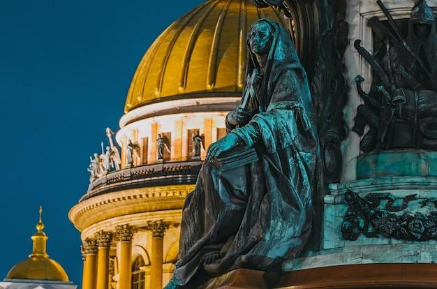 Vue nocturne des anciennes statues de stuc et du dôme de la cathédrale saint-isaac de saint-pétersbourg.