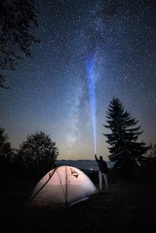 Vue nocturne épique du ciel étoilé avec une voie lactée dans un camping de montagne. un homme se tient près d'une tente et fait briller une lanterne sur les étoiles