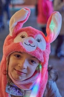Vue Nocturne D'une Jeune Fille Souriante Avec Un Chapeau Rose Avec Des Oreilles Illuminées à Noël à Tolède, Espagne Photo Premium