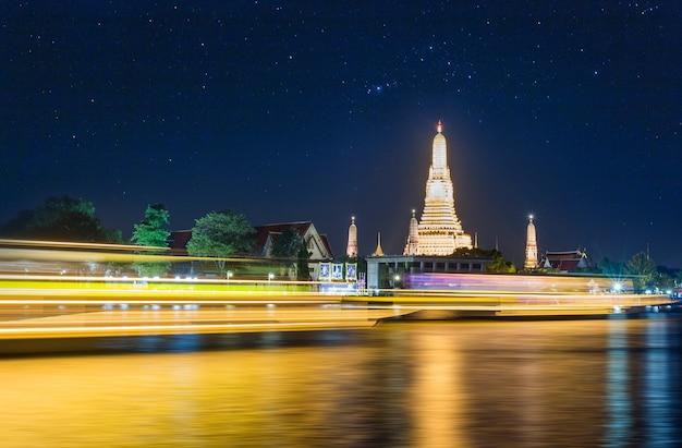 Vue nocturne de wat arun (temple) à travers la rivière chao phraya à bangkok, en thaïlande.