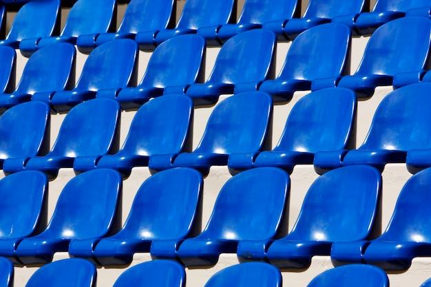 Vue de nombreux sièges en plastique bleu alignés sur un stade.