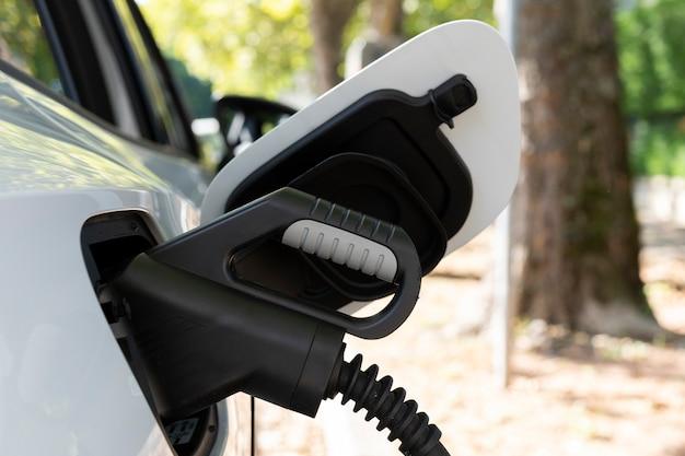 Vue de la nouvelle voiture électrique blanche en charge dans une station