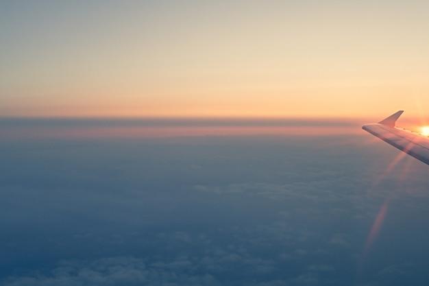 Vue sur les nuages du coucher du soleil à travers une fenêtre d'avion