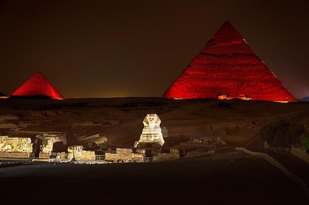 Vue de nuit sur les pyramides illuminées de gizeh, en egypte.