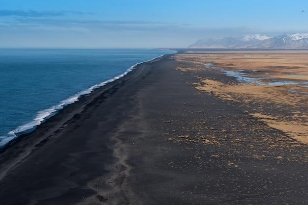Vue à l'ouest de dyrholaey sur la vaste plage de sable noir volcanique avec des montagnes
