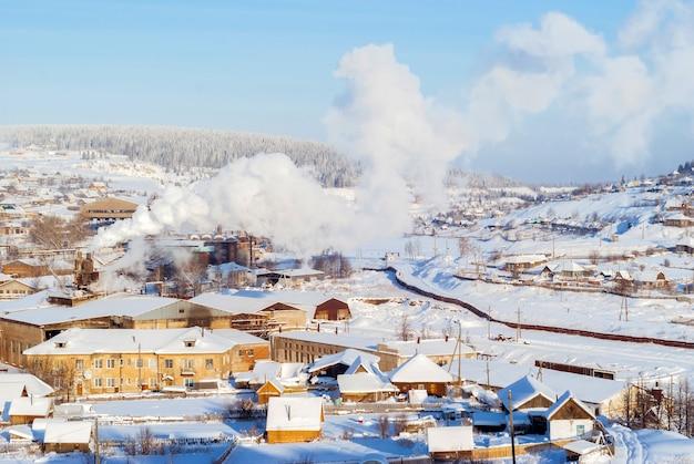 Vue sur l'oural avec une petite usine métallurgique dans la vallée de la rivière un jour d'hiver glacial