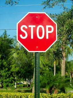 Une vue d'un panneau d'arrêt en été avec des arbres