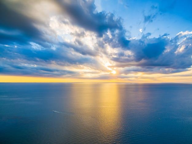 Vue panoramique aérienne de bateau solitaire naviguant à travers l'océan au beau coucher de soleil. belle lumière jaune éclatante se reflétant dans les eaux bleues de la baie.