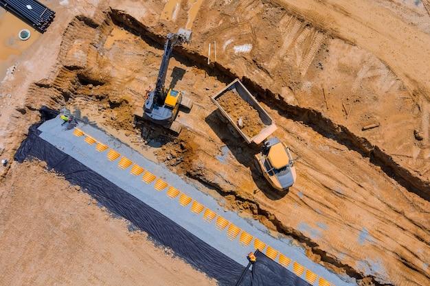 Vue panoramique aérienne de la tranchée de construction d'égouts pour la pose de la construction d'un système de drainage des eaux usées externe lors des travaux de terrassement