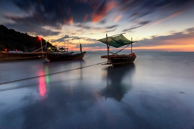 Vue panoramique des bateaux de pêche sur la plage pendant le coucher du soleil.