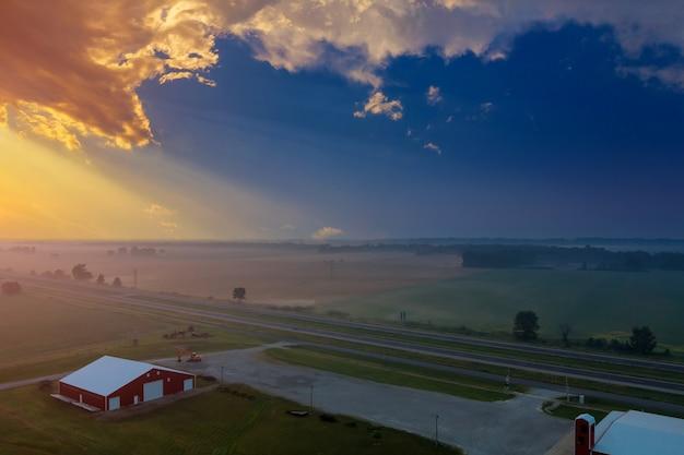 Vue panoramique avec une belle prairie de paysage de village brumeux dans le brouillard au lever du soleil tôt le matin