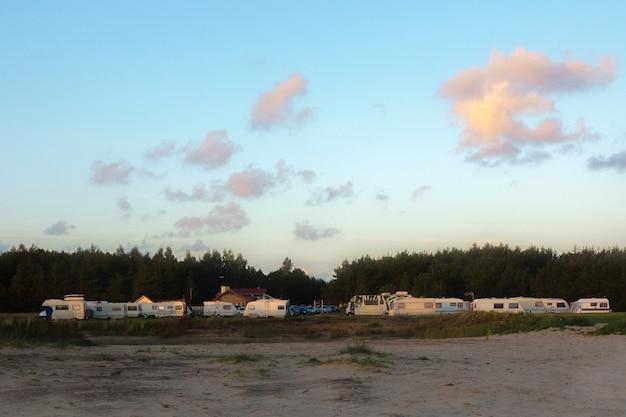 Vue panoramique d'une caravane ou d'un parc de roulottes à côté de bois au coucher du soleil d'été.