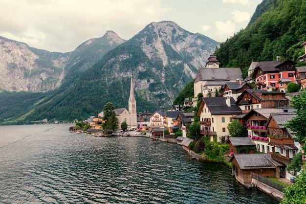 Vue panoramique sur carte postale du célèbre village de montagne de hallstatt dans les alpes autrichiennes avec navire à passagers dans la belle lumière du matin au lever du soleil sur une journée ensoleillée en été, région du salzkammergut, autriche