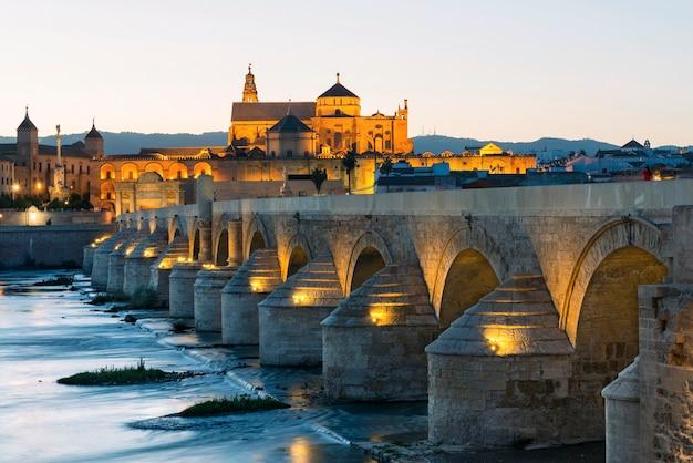 Vue panoramique sur le célèbre pont romain sur le fleuve guadalquivir et la mosquée-cathédrale illuminée au crépuscule à cordoue en espagne