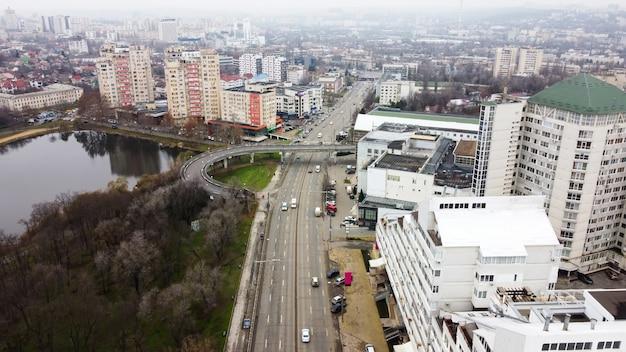 Vue panoramique de drone aérien de chisinau, rue avec plusieurs bâtiments résidentiels et commerciaux, route avec des voitures en mouvement, lac aux arbres nus