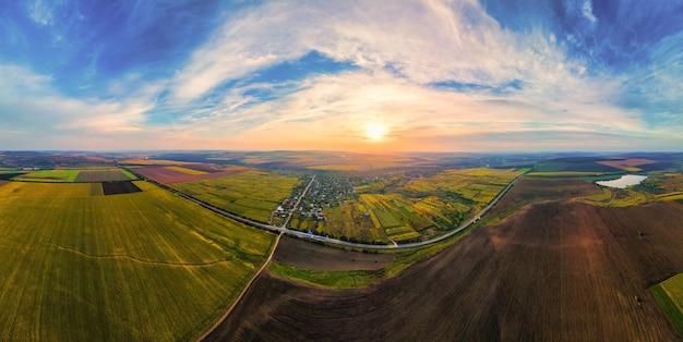 Vue panoramique de drone aérien de la nature en moldavie au coucher du soleil. village, lac, vastes champs