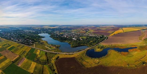 Vue panoramique de drone aérien de la nature en moldavie au coucher du soleil. village, lacs, vastes champs
