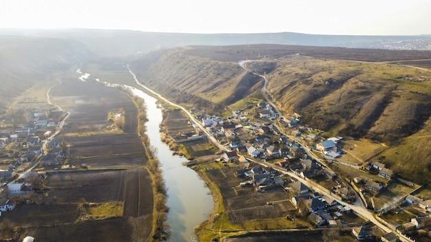 Vue panoramique de drone aérien d'un village situé près d'une rivière et de collines, champs, brouillard dans l'air, moldavie