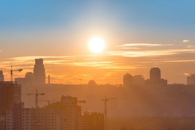 Vue panoramique du coucher du soleil dans la ville avec la silhouette des bâtiments et des grues industrielles