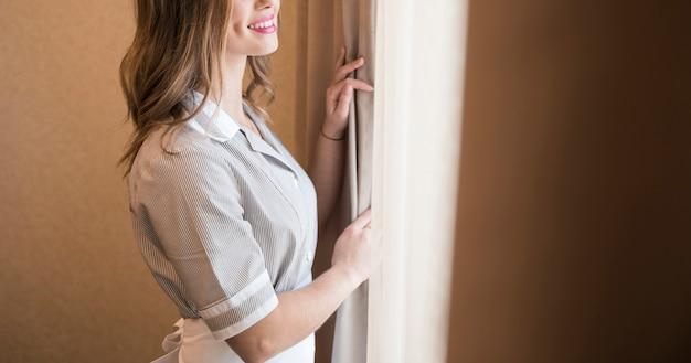 Vue panoramique d'une femme de ménage souriante debout près du rideau