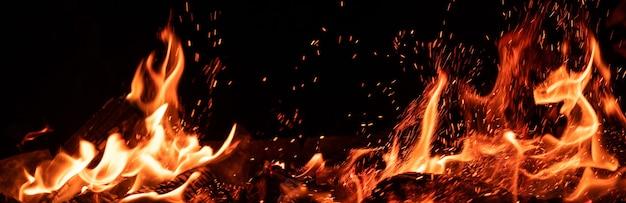 Vue panoramique de la flamme brûlante et des étincelles sur fond noir
