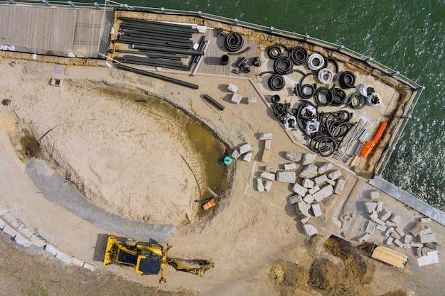 Vue panoramique de la jetée du service de réparation sur les tuyaux noirs en plastique posés sur la jetée en bois qui s'écoule