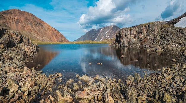 Vue panoramique sur un lac de montagne bleu et propre dans l'altaï avec des tentes sur le rivage. beau lac turquoise. lac transparent inhabituel en automne.