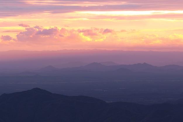 Vue panoramique des montagnes silhouette contre le ciel au coucher du soleil et faisceau
