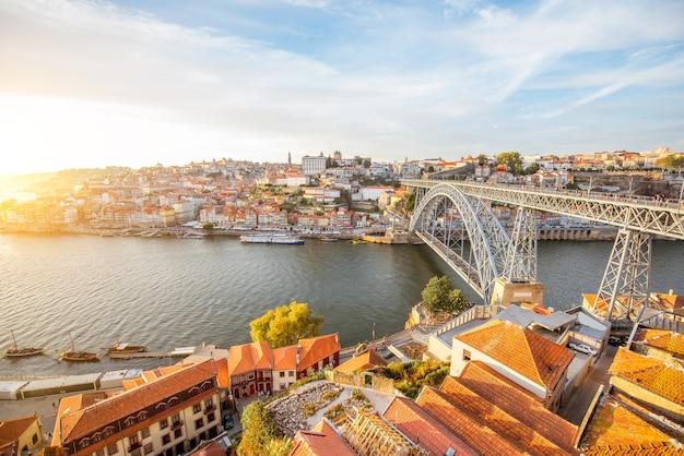 Vue panoramique sur le paysage de la vieille ville avec le fleuve douro et le célèbre pont de fer dans la ville de porto pendant le coucher du soleil au portugal