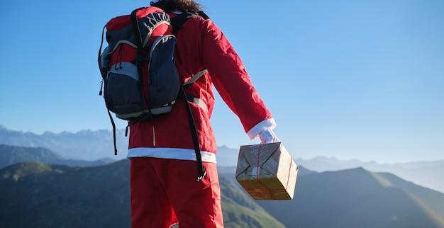 Vue panoramique d'un père noël méconnaissable avec un sac à dos portant un cadeau sur une montagne