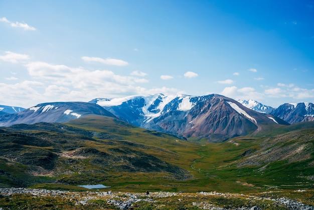 Vue panoramique sur petit lac alpin et grandes montagnes avec glacier au soleil.