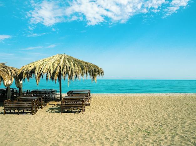 Vue panoramique sur la plage de sable avec un café en plein air sur fond bleu de la mer et du ciel