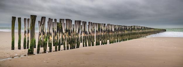 Vue panoramique de planches de bois verticales dans le sable d'un quai en bois inachevé à la plage