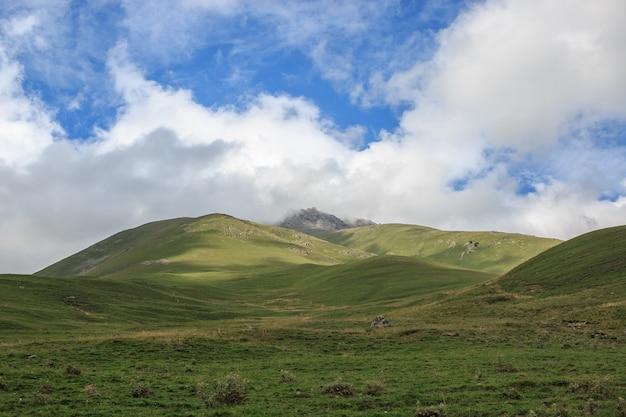 Vue panoramique des scènes de montagnes dans le parc national dombay, caucase, russie, europe. ciel bleu dramatique et paysage d'été ensoleillé