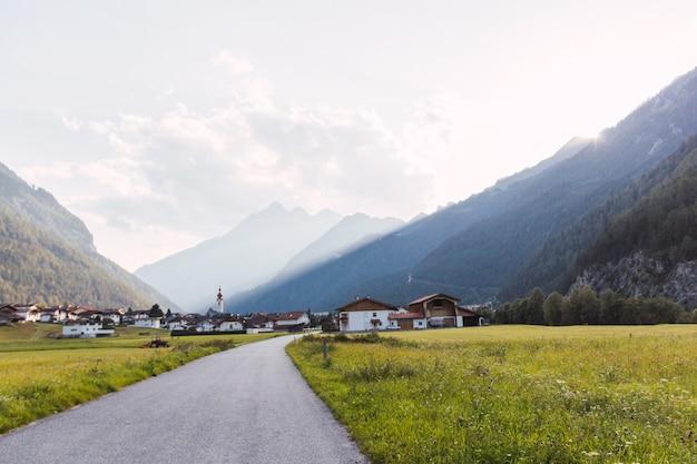 Vue panoramique d'un village dans les alpes autrichiennes à partir d'une route avec des rayures de soleil qui traverse les montagnes